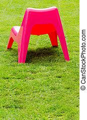 Červené plastové křeslo na zelené trávě
