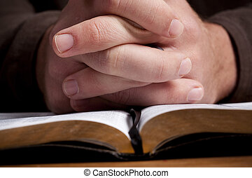 Člověk se modlí s biblemi