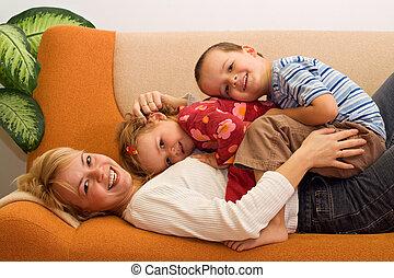 Šťastná žena a děti se baví doma