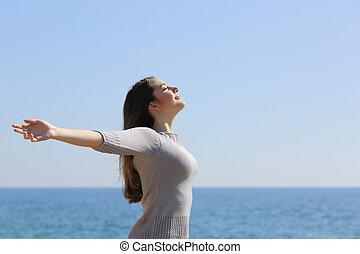 Šťastná žena dýchá na čerstvý vzduch a zvedá ruce na pláž