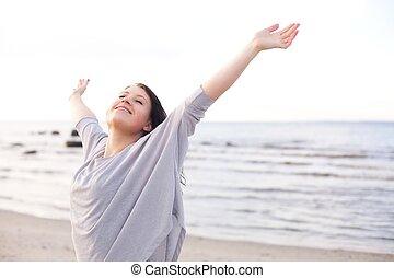 Šťastná žena, která si natahuje ruce, aby si užívala přírody