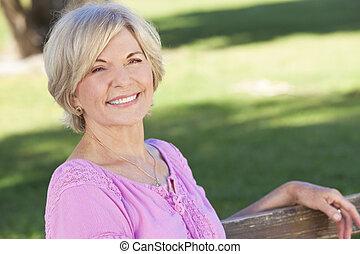 Šťastná žena sedící venku a usmívá se