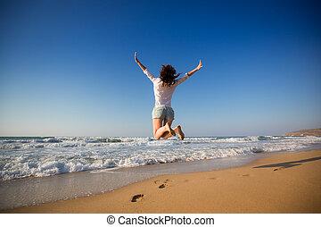 Šťastná žena skákala na pláži