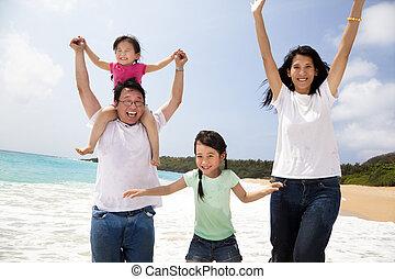 Šťastná asianská rodina skáče na pláži