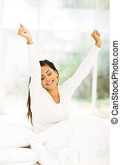 Šťastná mladá žena se probouzí
