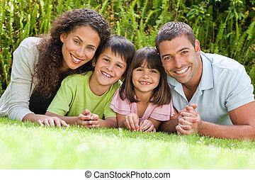 Šťastná rodina ležící na zahradě