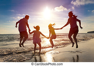Šťastná rodinka, která se skáčí na pláži