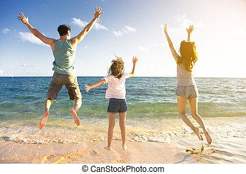 Šťastná rodinka skákající na pláži