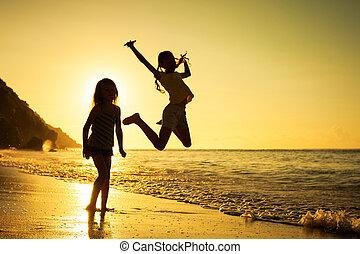 Šťastné děti hrající na pláži při západu slunce