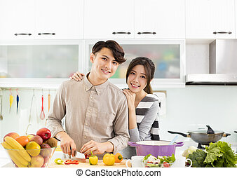 Šťastný asijský pár v kuchyni