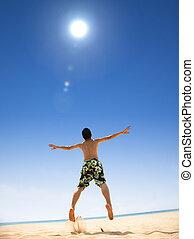Šťastný mladý muž skákající na pláži