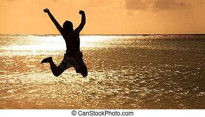 Šťastný mladý muž skákající na pláži při západu slunce