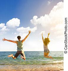 Šťastný mladý pár, co skáče na pláži