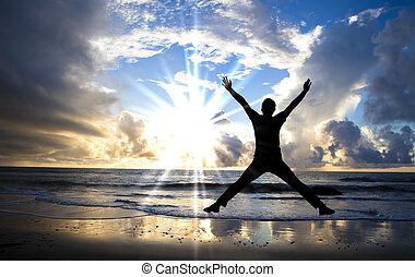 Šťastný muž skákající na pláži s krásným východem slunce