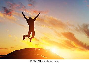 Šťastný muž skákající na vrcholu hory západu slunce. Úspěch
