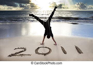 Šťastný nový rok 2011 na pláži slunce. Mladý muž se drží a oslavuje.