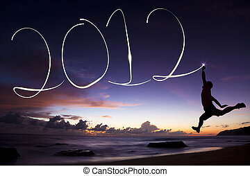 Šťastný nový rok 2012. Mladý muž skáče a kreslí si na pláži před svítáním