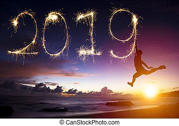 Šťastný nový rok 2019. Skákání a kreslení na pláži