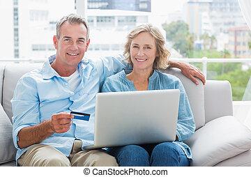 Šťastný pár, který sedí na gauči a používá laptop, aby se mohl nakupovat doma v obýváku