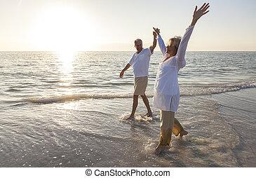 Šťastný starší pár, co drží při západu slunce