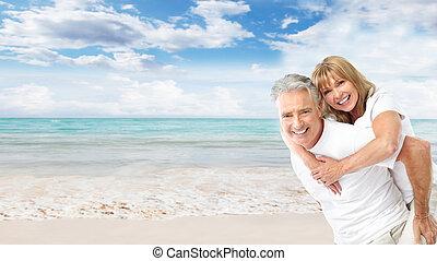 Šťastný starší pár na pláži.