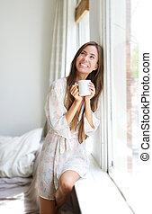 Žena, která se směje oknem, pije čaj