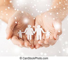 Žena má ruce s papírovou rodinou