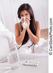 Žena nemocná v posteli s rýmou a chřipkou