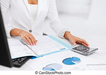 Žena s kalkulátorem a papíry