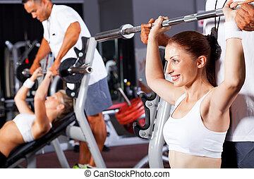 Žena s osobním trenérem v tělocvičně