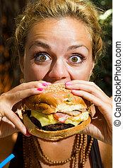Ženský jí cheeseburger