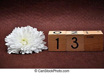 13 june na dřevěných kostech s bílým popelem na hnědém pozadí