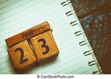 23. června. Den 23 měsíců, ručně dělaná dřevěná kostka s měsícem a den nasazená do modrého pozadí. Umělá barva. Letní měsíc, den roku