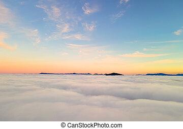 Aeriální pohled nad bílými oblaky ve žlutém západu slunce a vzdálených horách.