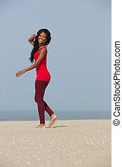 Africká americká žena, co chodí po pláži
