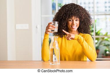 Africká americká žena, která pije sklenici vody doma, velmi šťastná, když ukazuje prstem a rukou