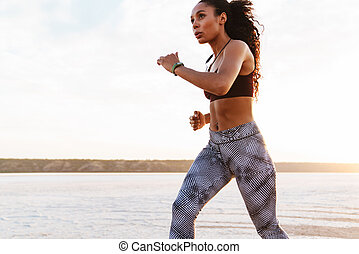 Africká americká sportová žena, která běhá po pláži