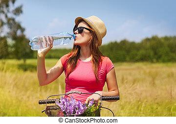 Aktivní žena, která pije vodu z motorky
