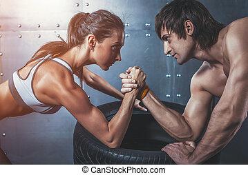 Athle svalnatá muž a žena s rukou s rukou, která se střetla s rukou a zápasila s mladým párem, který se hodí na sportovní styl.