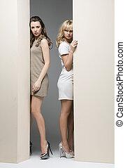 Atraktivní ženy skrývající se za zeď