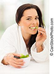 Atraktivní mladá žena jí salát