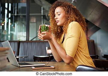 Atraktivní mladá žena sedící v kavárně a pije čaj