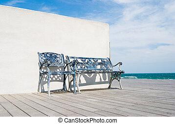 Bench na dřevěné podlaze na pláži.
