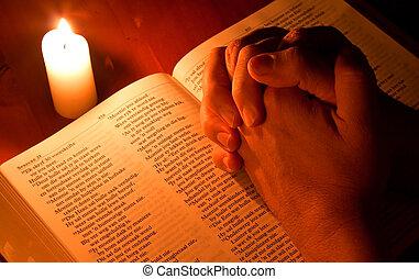 Bible svíceným světlem s rukama pomodlením
