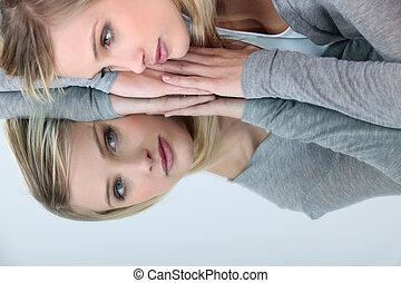 Blonďanka se dívá do zrcadla