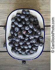 Blueberries v rezavé kuchyni s dřevěným pozadím