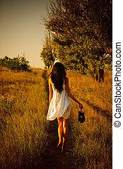 Bosá dívka v bílých šatech s botami v ruce je na poli. Zadní výhled