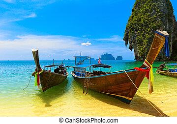 Cestovní krajina, pláž s modrou vodou a nebem. Thajská příroda, krásný ostrov a tradiční dřevěná loď. Scénářské tropické ráje.