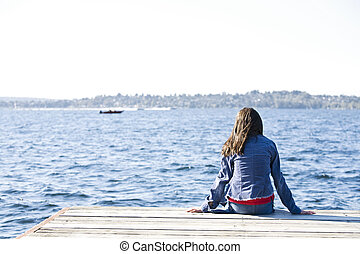 Dívka sedící v přístavu u jezera a dívá se přes vodu.