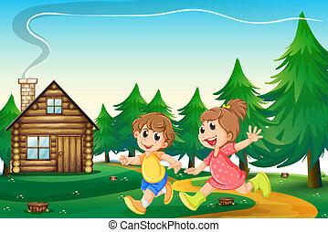 Děti hrající za dřevěným domem na kopci